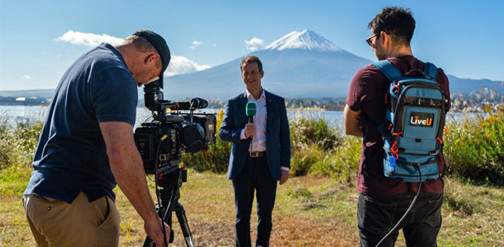 Reporter informing with a view of Mt. Fuji with a LiveU backpack transmission device