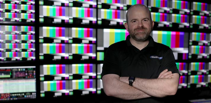 Adam Mills from High End TV at front of a videowall